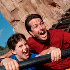 A father and son enjoy a thrill ride at a Disney Park.